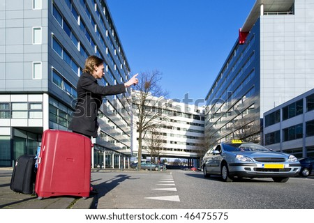 A businessman with several suitcases flagging a taxi