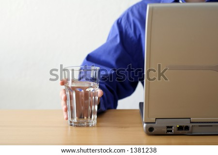 A businessman working on a laptop and holding a glass of water