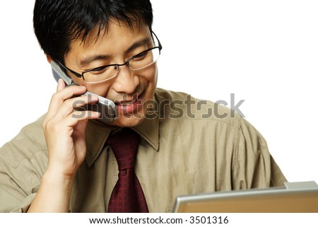 A businessman working on his laptop while making a phone call