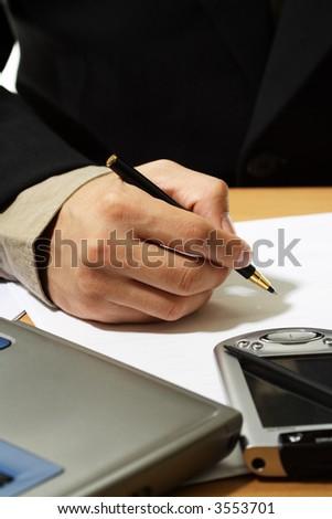 A businessman writin on a piece of paper
