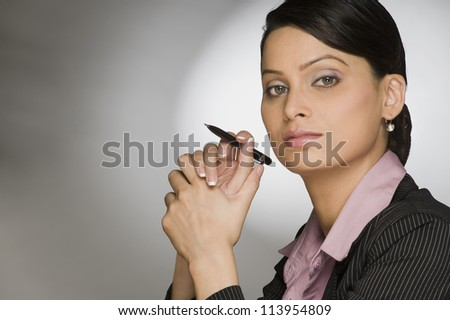 A businesswoman holding a pen