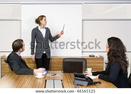 A businesswoman holding a presentation for two of her colleagues