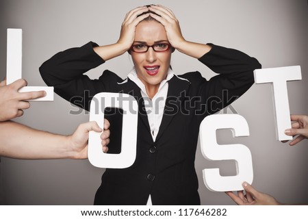 A businesswoman holding her head in frustration implying that she is lost in the financial turmoil. Woman lost.