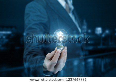A businesswoman is holding a shining lightbulb with a currency unit inside at the dark background. The concept is the profitable financial idea. Foto stock ©