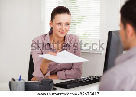A businesswoman is presenting a contract to a customer