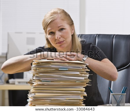 A businesswoman is seated at a desk with a large stack of paperwork in front of her.  She is looking at the camera.  Horizontally framed shot.