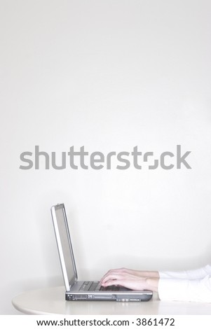 a businesswoman is sitting at her desk using her laptop and working with a close-up of her hands on the laptop