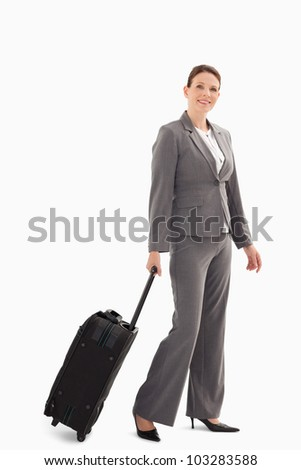A businesswoman is walking with a suitcase