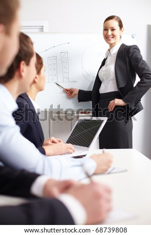 A businesswoman pointing at whiteboard before her colleagues