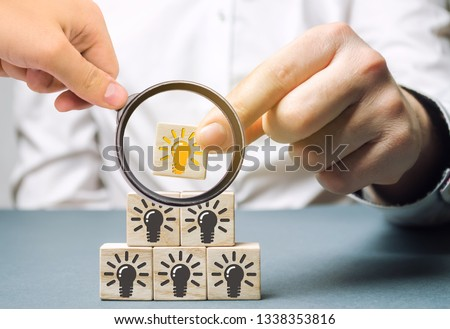 A businesswoman puts wooden blocks with a light bulb of an idea. Innovation and new fresh solutions. Inspiration of other team members. Business process, systematization. Creative process. Stock photo ©