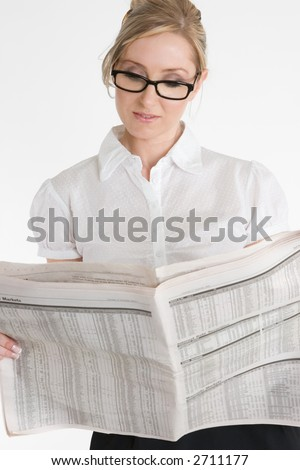 A businesswoman reading the financial newspaper.  Please note newsprint has been artificially blurred to render company names illegible.
