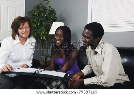 A Businesswoman Showing A Document To A Couple