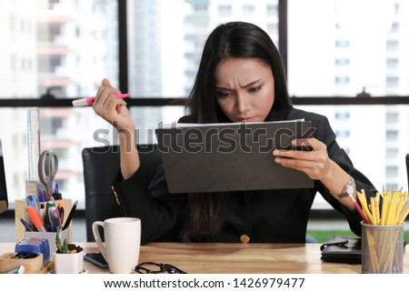 A businesswoman sitting in office and writing and concentrate serious looking in paper chart result  #1426979477