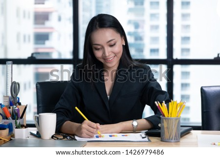 A businesswoman sitting in office and writing and concentrate serious looking in paper chart result  #1426979486