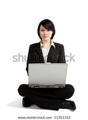 A businesswoman sitting on the floor working on her laptop