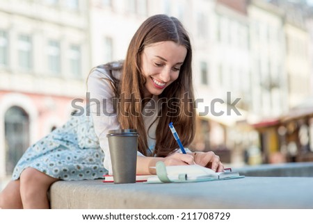 Shutterstock A businesswoman sitting on the fountain with a coffee cup against urban scene.
