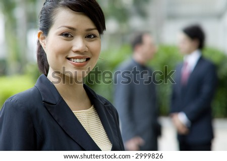 A businesswoman standing in front of two male colleagues (shallow depth of field used)
