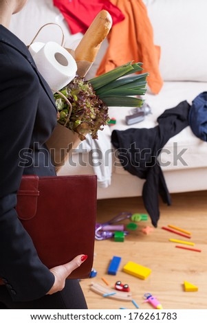A businesswoman standing in messy home with shopping bags