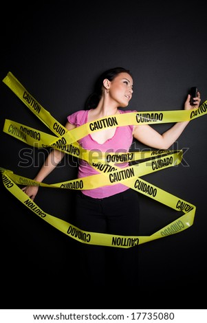 A businesswoman trapped in yellow caution tape trying to talk on her cellphone