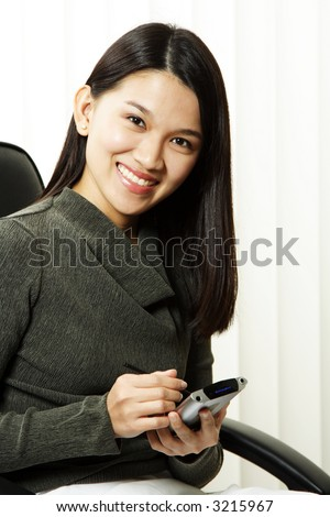 A businesswoman using her PDA at the office