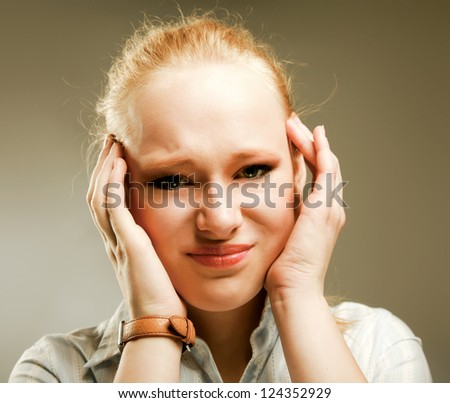 A businesswoman with a headache holding head, isolated on grey background