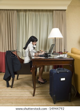A businesswoman works late into the night on a laptop in her hotel room while on a business trip.