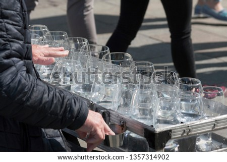 A busker, street performer, musician playing an unusual uncommon instrument made from wine glasses - glass harp. Concept of free street art performance and busking #1357314902