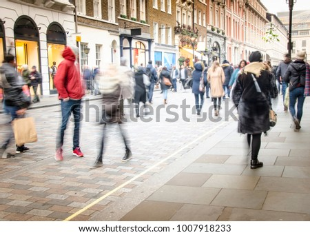 A busy high street with anonymous crowds of shoppers with shopping bags #1007918233