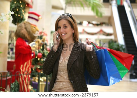 A busy woman Christmas shopping and talking on the phone
