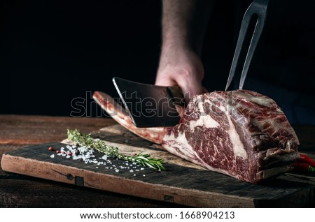 A butcher cuts beef Tomahawk steak on a bone with a cleaver on a wooden cutting Board on a dark background