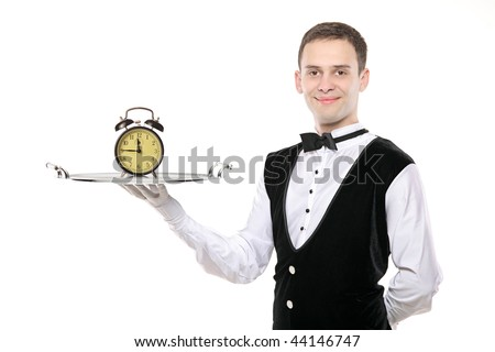 A butler holding a silver tray with a alarm clock on it