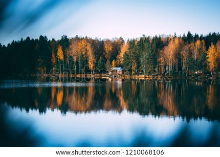 A cabbin by the lake, seen through a pine branch. The water is almost perfectly still. Autumn season with green, yellow and orange trees in contrast with the blue lake and sky.