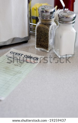 A cafe or restaurant table top background with salt and pepper shakers, napkin holder, guest check etc,