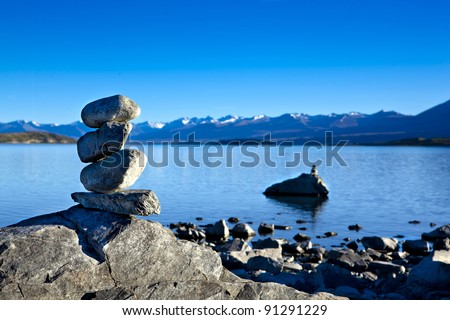 a cairn placed on a rock at lake tekapo
