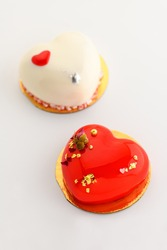 A cake in heart shape. Two heart-shaped cupcakes on a white background. Valentine's Day. Vertical photo