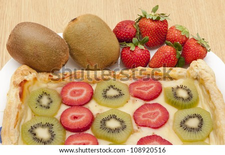 a cake, made with slices of kiwi and strawberry