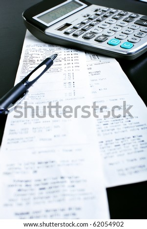 A calculator, a pen, bills, receipts on the black table