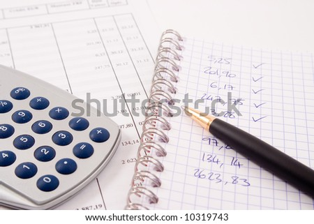 A calculator, a pen, glasses and a book