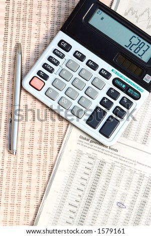 A calculator and a pen on top of a financial newspaper.