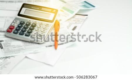 A calculator , ball pen and household bills , adding light  #506283067