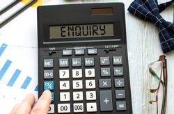 A calculator labeled ENQUIRY lies on financial documents in the office.
