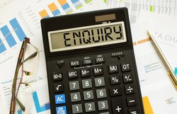 A calculator labeled ENQUIRY lies on financial documents in the office. Business concept.