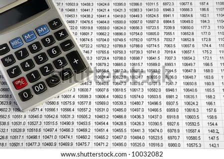 A calculator on a business data sheet print out. - stock photo