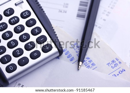A calculator, pen, and financial statement, blue tone