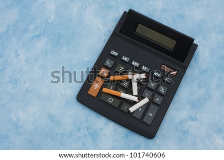 A calculator with a broken cigarettes on a blue background, Calculating the cost of smoking
