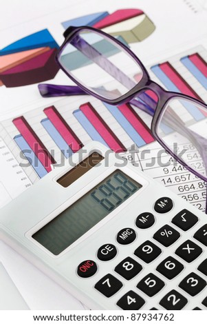a calculator with graphics of a balance sheet. sales, profit and operating costs.