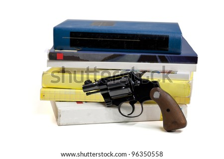 A 38 caliber pistol stands in front of school textbooks, isolated on white, focus on gun handle