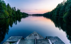 A calm and silent evening at sunset at a small forest lake in Sweden. In the foreground there is a wooden bridge. The lake is surrounded by trees that are reflected in the water