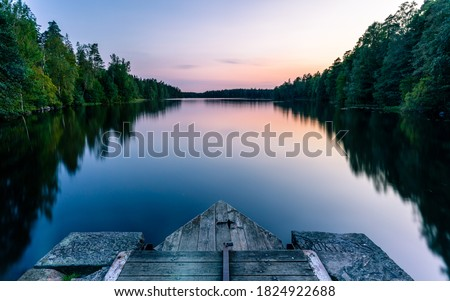 A calm and silent evening at sunset at a small forest lake in Sweden. In the foreground there is a wooden bridge. The lake is surrounded by trees that are reflected in the water Сток-фото ©