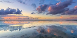 A calm and tranquil zen-like sunset at the beach with beautiful colours in pink and red with reflections on the water - Wadden sea, The Netherlands
